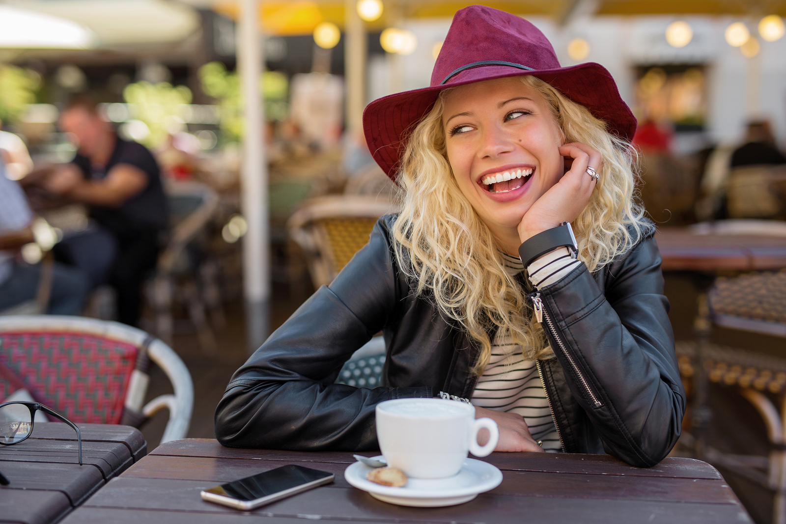 Beautiful woman with red hat laughing while on coffee break