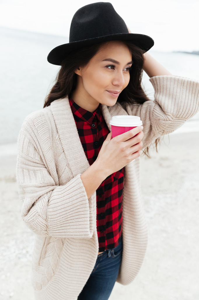 Young brunette woman with cup of coffee walking near sea