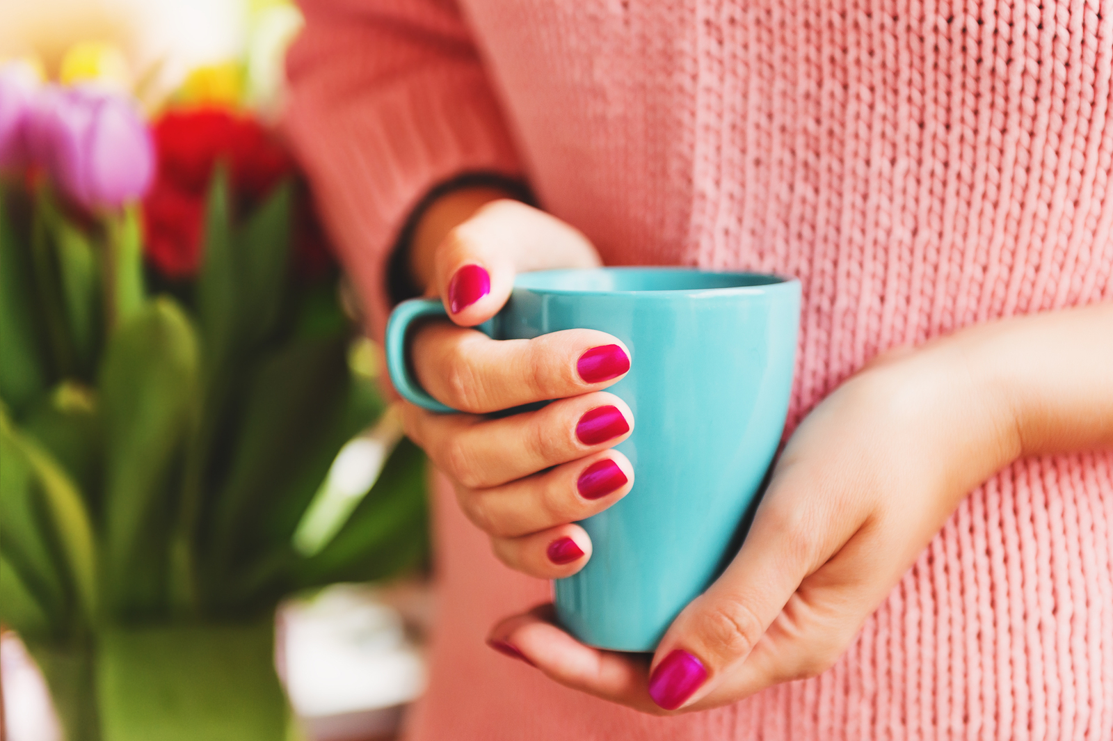 Cup of coffee in woman's hands with bright pink manicure