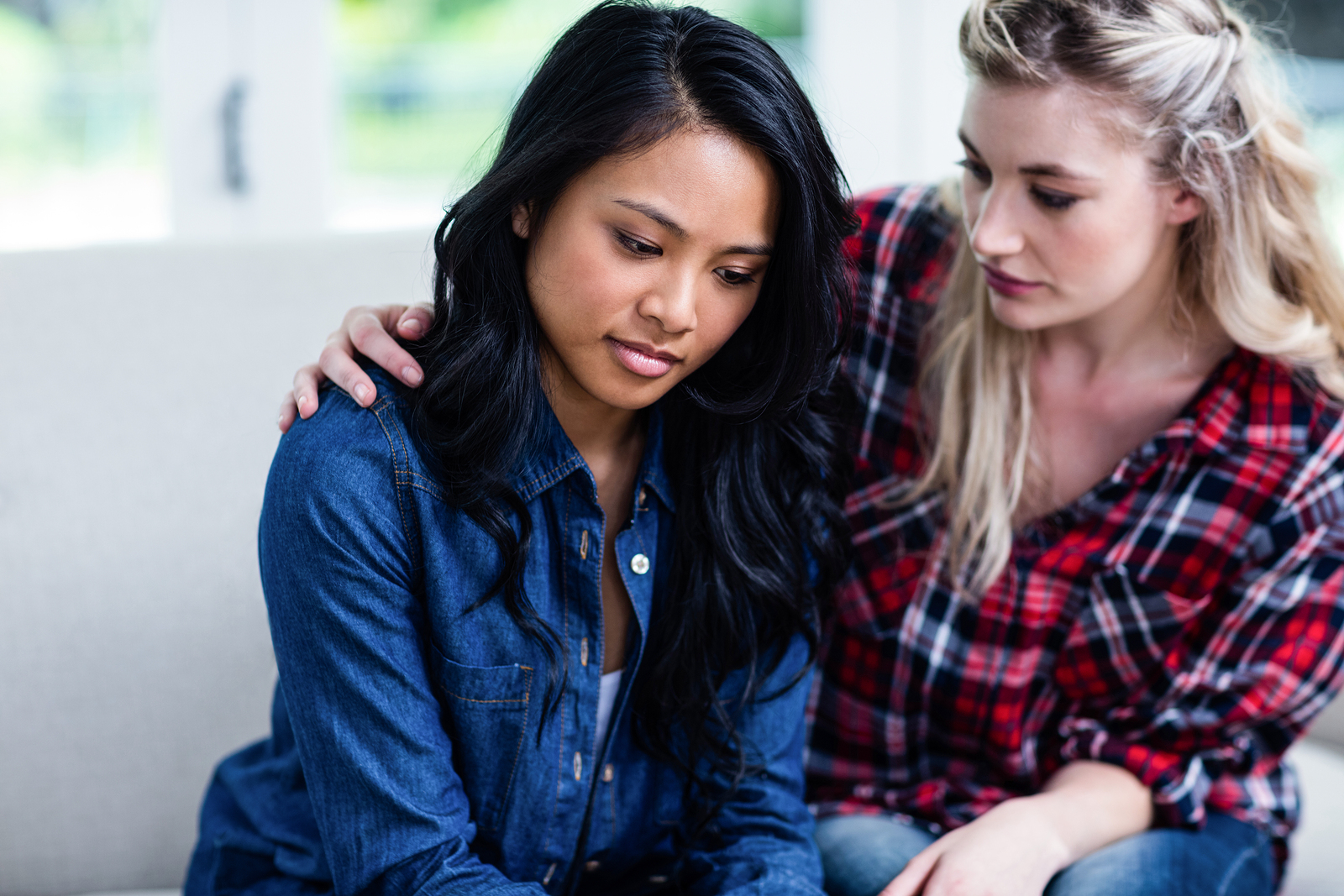 Close-up of young woman consoling depressed female friend at hom